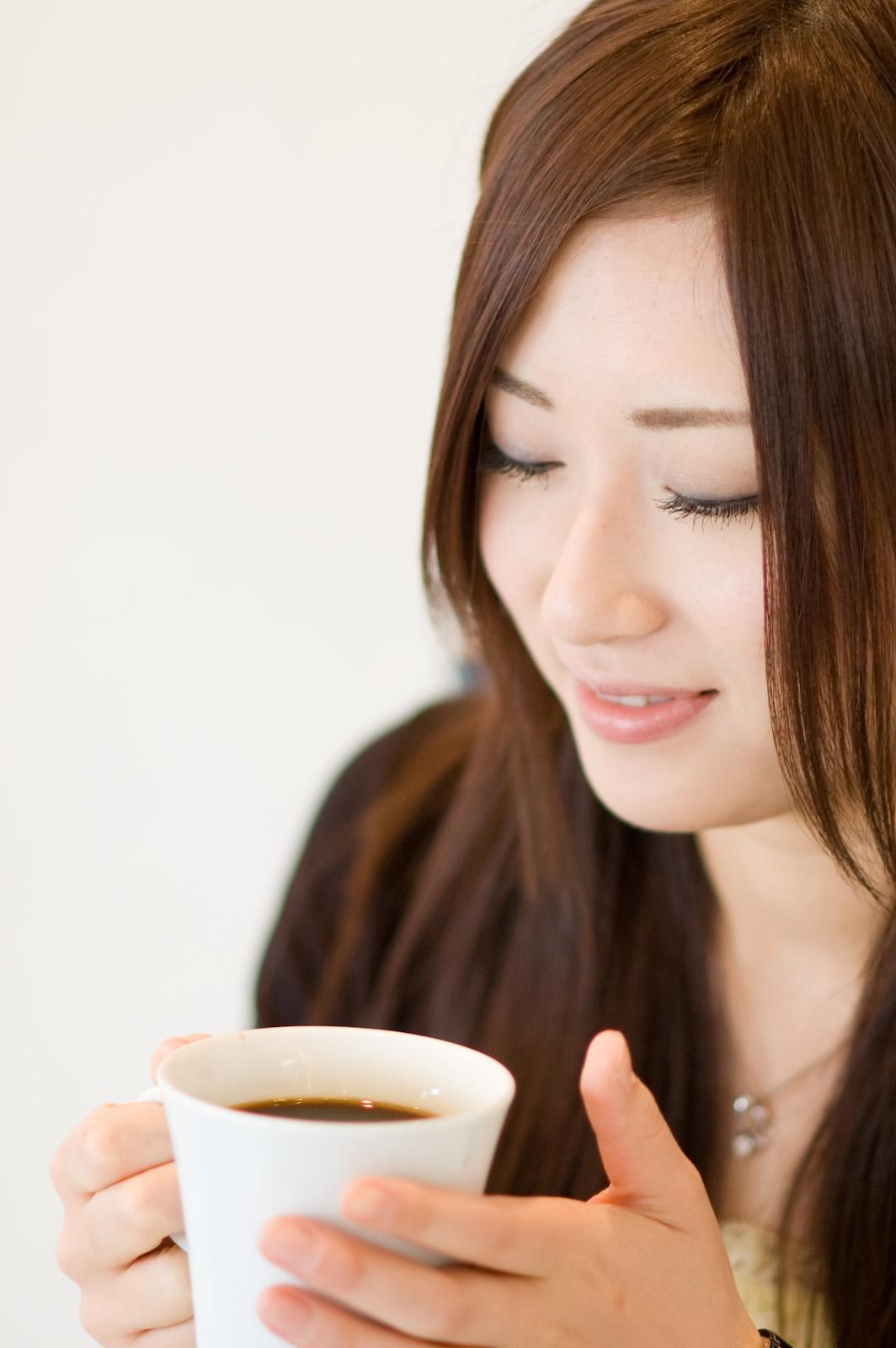 コーヒーカップを持つ