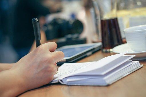 ノートにペンで書く姿