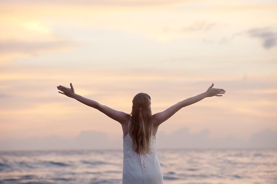海を向かい手を広げる