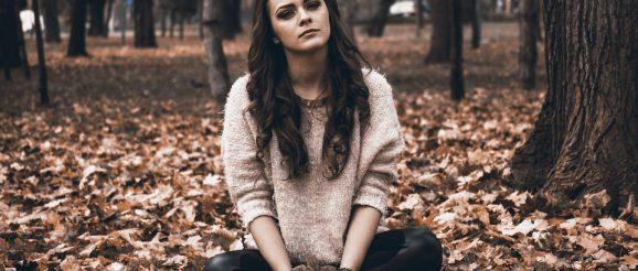 枯れ葉の上に座る女性