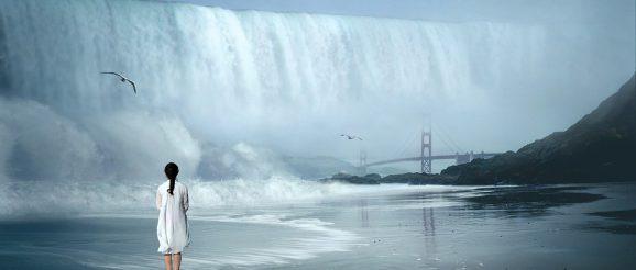 海の前で滝を見る女性