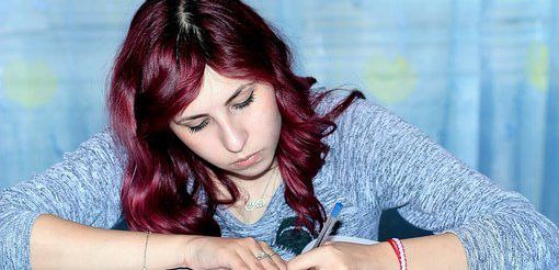 ノートにペンで書く女性