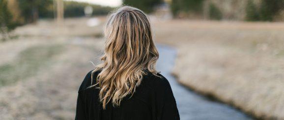流れる川を見つめる女